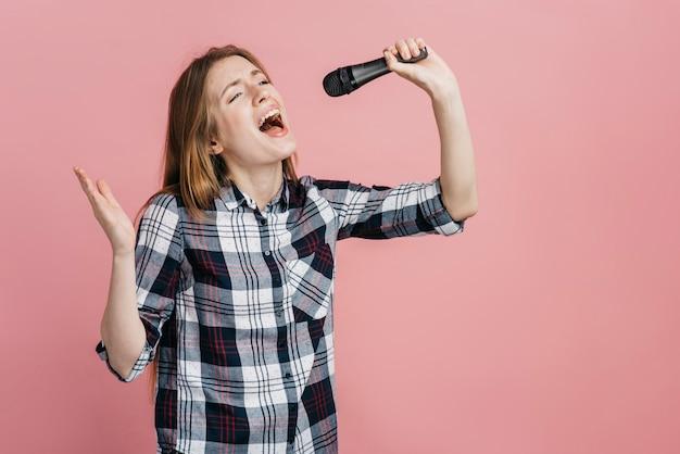 Vrouw het zingen bij de microfoon met exemplaarruimte Premium Foto
