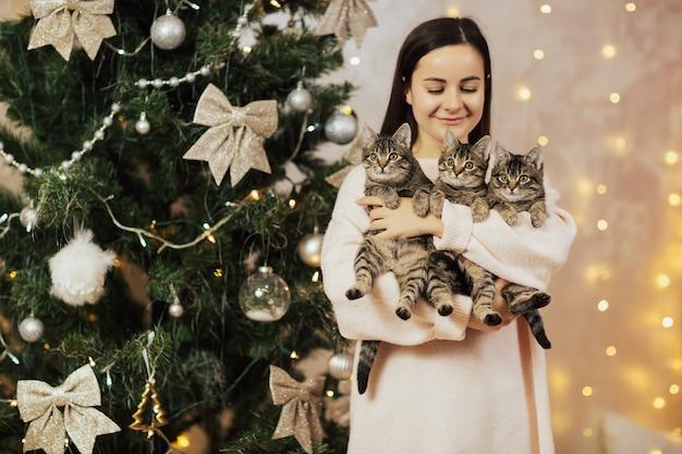 Vrouw houden en kijken naar haar drie kittens Premium Foto