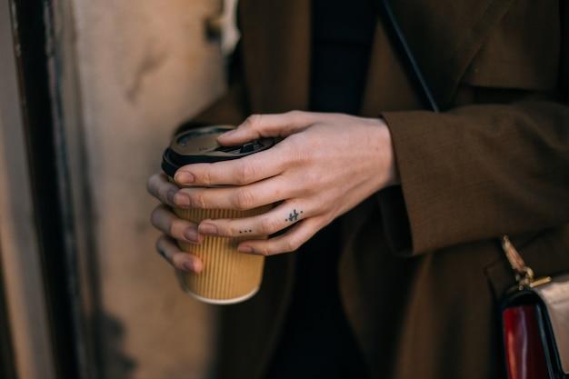 Vrouw houdt afhaalmaaltijden om koffiekopje op straat te gaan Gratis Foto