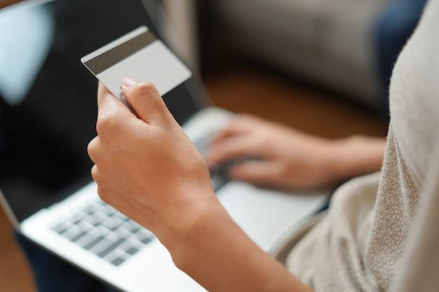 Vrouw houdt creditcard met computer online winkelen en betalen Premium Foto