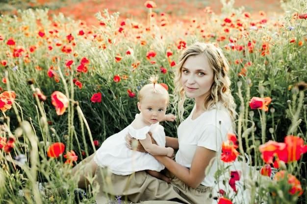 Vrouw houdt haar baby onder papaverveld Gratis Foto