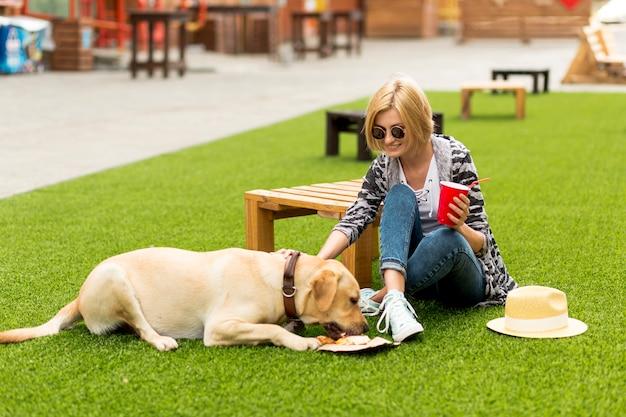 Vrouw huisdieren haar hond in het park Gratis Foto