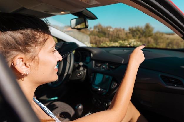 Vrouw in auto die en vooruit hand glimlacht toont Gratis Foto