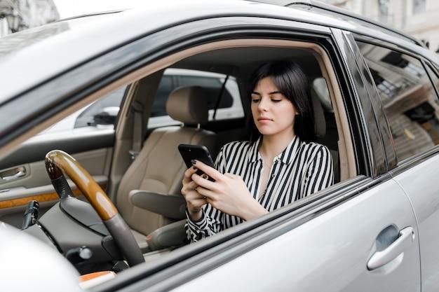 Vrouw in auto maakt gebruik van telefoon Premium Foto