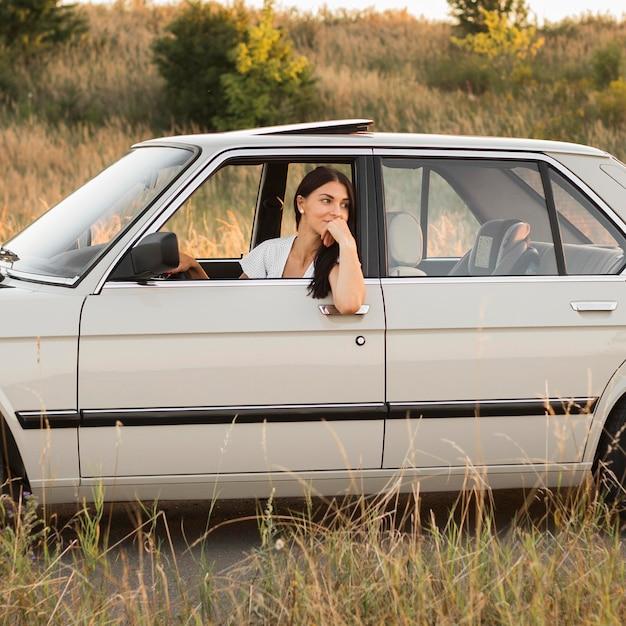 Vrouw in auto poseren in veld Gratis Foto