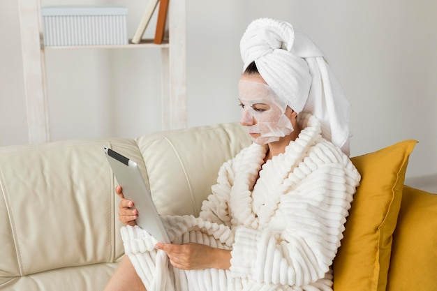 Vrouw in badjas met gezichtsmasker met haar tablet Gratis Foto
