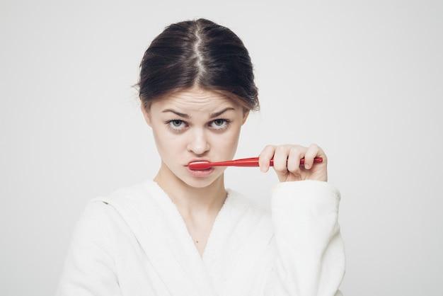 Vrouw in badjas tanden poetsen Premium Foto