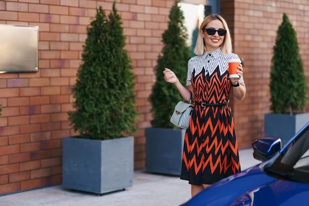 Vrouw in beweging met een kopje koffie tijdens het wandelen in de buurt van een auto in de stad Gratis Foto