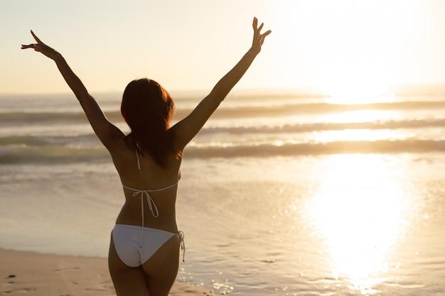 Vrouw in bikini die zich met wapens omhoog op het strand bevindt Gratis Foto