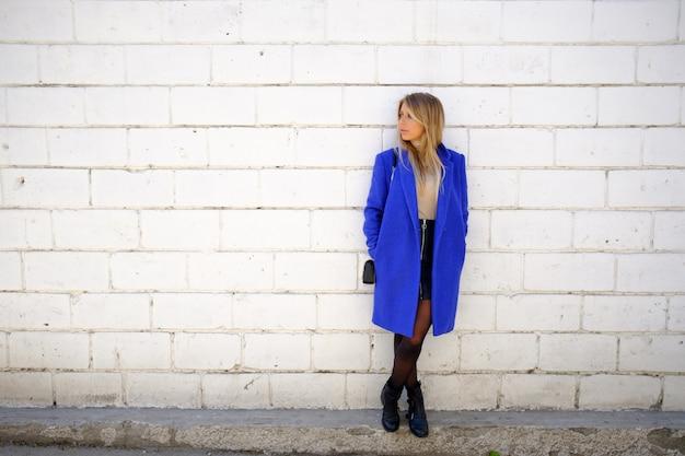 Vrouw in de blauwe jas op straat Gratis Foto