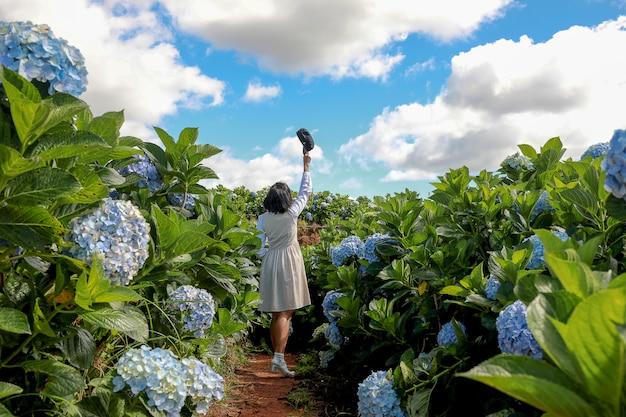 Vrouw in de kleurrijke tuin van de hydrangea hortensiabloem met blauwe hemel en wolkenachtergrond. Premium Foto