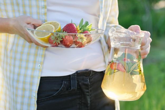 Vrouw in de natuur houden pot aardbeien munt en citroen Premium Foto