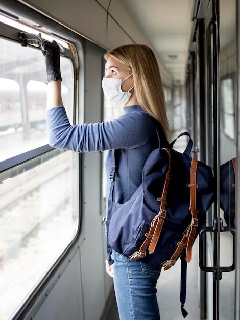 Vrouw in de trein met masker Gratis Foto