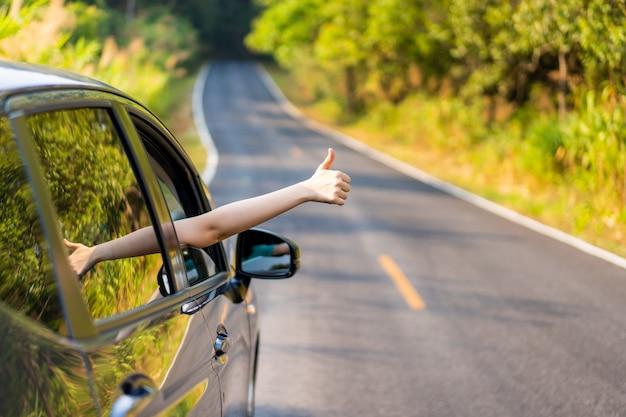 Vrouw in een auto die een teken doet Premium Foto