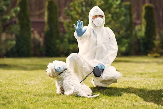Vrouw in een beschermend pak wandelen met een hond Gratis Foto