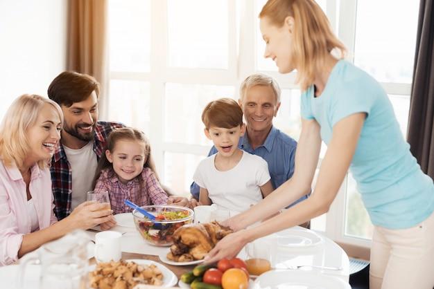 Vrouw in een blauw t-shirt geeft de gebakken kalkoen aan tafel. Premium Foto