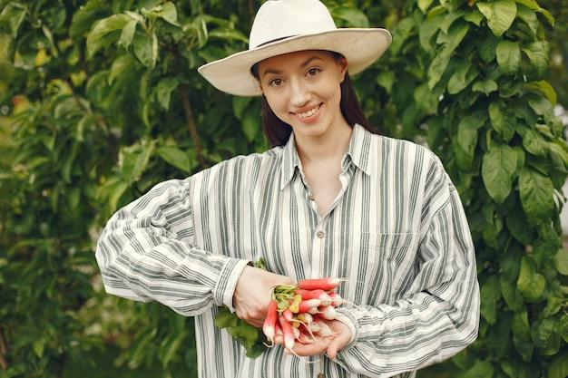 Vrouw in een hoed die verse radijzen houdt Gratis Foto
