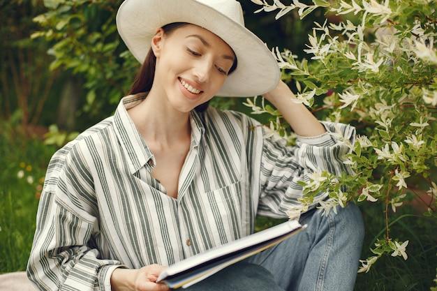 Vrouw in een hoed met een boek in een tuin Gratis Foto