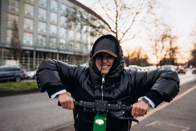 Vrouw in een jasje op een elektrische scooter in een herfststad. rijden op elektrische voertuigen bij koud weer. Gratis Foto