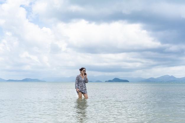 Vrouw in een jurk in het zeewater staan en praten over de mobiele telefoon. Premium Foto