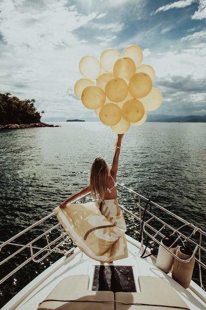 Vrouw in een jurk staande op een jacht, met gouden ballonnen tijdens het zeilen Gratis Foto