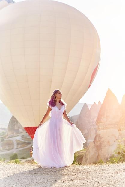 Vrouw in een lange jurk op de achtergrond van ballonnen in cappadocië Premium Foto
