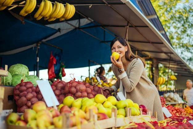 Vrouw in een markt op de plank voor fruit dat voor kruidenierswinkels winkelt, zij controleert de appelen. Premium Foto