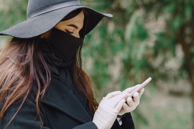 Vrouw in een masker staat op straat Gratis Foto