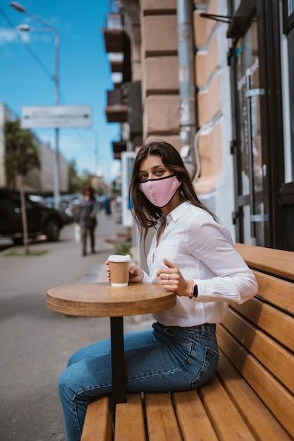 Vrouw in een medisch masker drinkt koffie op straat Gratis Foto