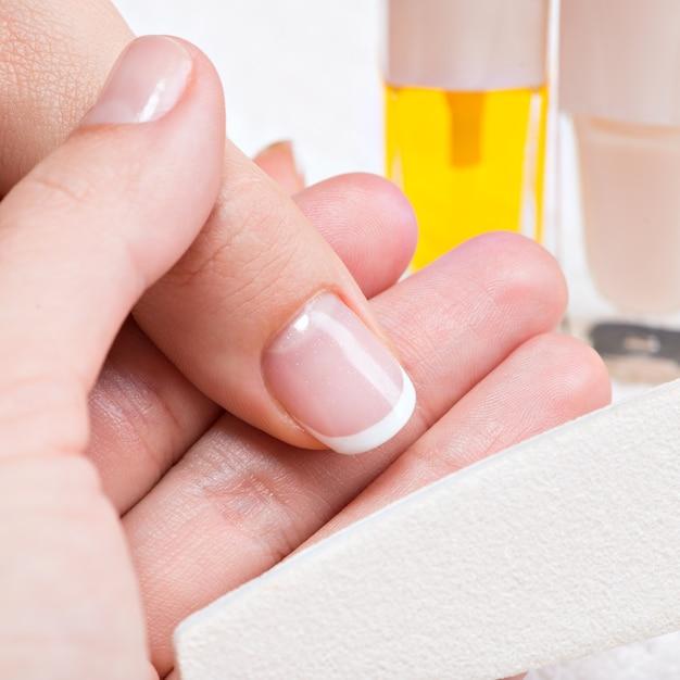 Vrouw in een nagel salon manicure ontvangen. schoonheidsspecialiste die nagellak op een miniatuur toepast. Gratis Foto