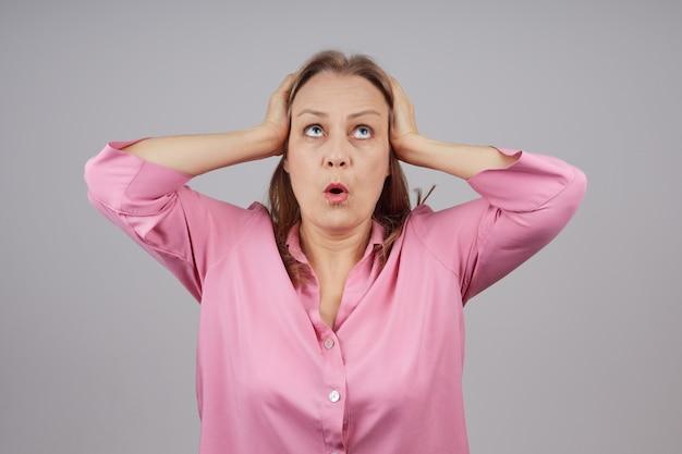Vrouw in een roze shirt met haar hoofd met haar handen. Premium Foto