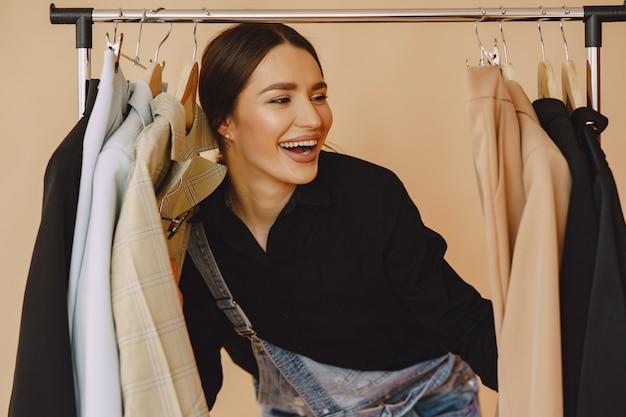 Vrouw in een studio met veel kleding Gratis Foto