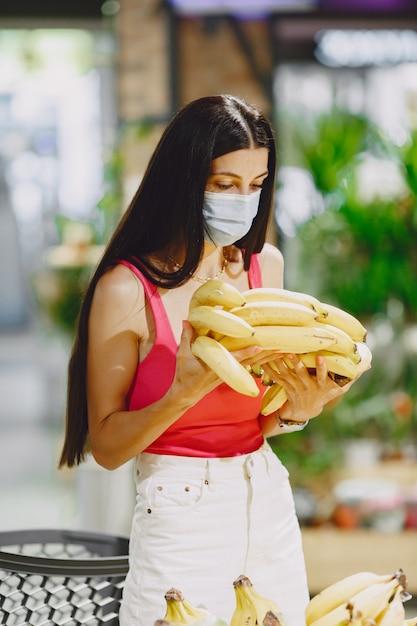 Vrouw in een supermarkt. dame in een gasmasker. meisje maakt parchases. Gratis Foto