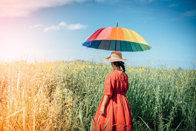 Vrouw in een weide met een paraplu Gratis Foto