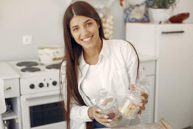 Vrouw in een wit overhemd dat zich in rhekeuken bevindt met havermeel Gratis Foto