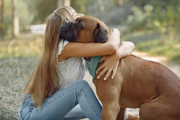 Vrouw in een zomer bos spelen met hond Gratis Foto
