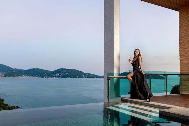 Vrouw in een zwarte lange jurk staat met een glas champagne in de buurt van het zwembad Premium Foto