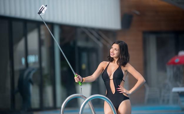 Vrouw in een zwarte sexy zwembroek, nemen selfie foto met monopod Premium Foto