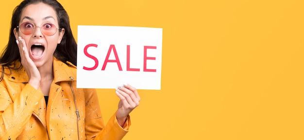 Vrouw in geel jasje kopie ruimte verkoop concept Gratis Foto