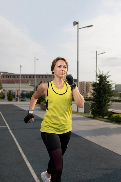 Vrouw in gele en zwarte sportuitrustingen opleiding, die in de straat lopen. Gratis Foto