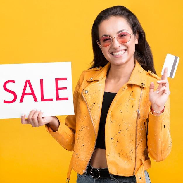Vrouw in gele jas verkoop banner en creditcard Gratis Foto