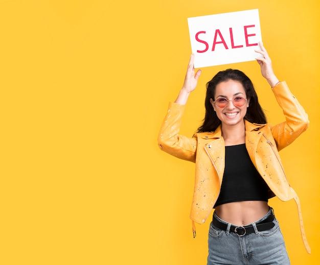 Vrouw in gele jas verkoop banner kopie ruimte Gratis Foto