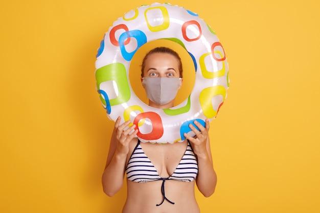 Vrouw in gestreept zwempak die door rubberring kijken, die hygiënisch gezichtsmasker dragen om virus op het strand van het toevlucht, rust en de zomervakantie te voorkomen met middelen om haar gezondheid te beschermen. Gratis Foto