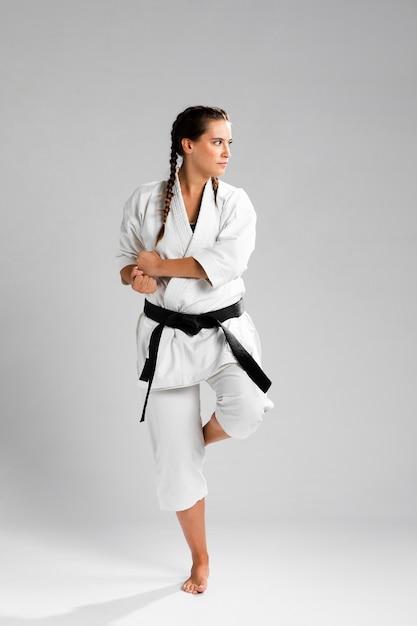 Vrouw in gevechtspositie die het witte uniform op grijze achtergrond draagt Gratis Foto