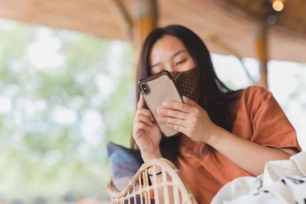 Vrouw in gezichtsmasker met behulp van haar mobiele telefoon zittend in een stoel. Premium Foto