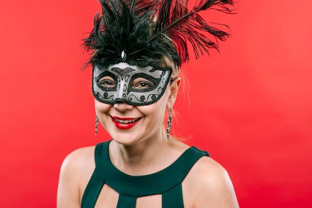 Vrouw in grijs masker met veren lachen Gratis Foto