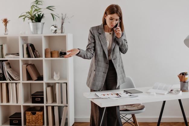 Vrouw in grijs pak praten over de telefoon met zakelijke partners. portret van volwassen dame grafiek kijken. Gratis Foto