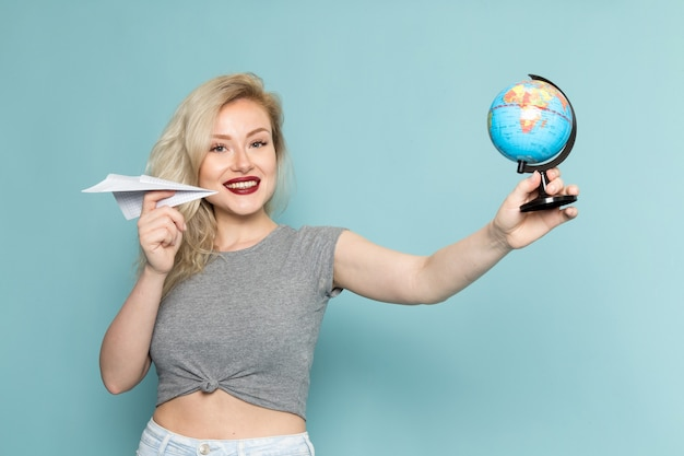 Vrouw in grijs shirt en heldere blauwe spijkerbroek met papieren vliegtuigje en kleine wereldbol Gratis Foto