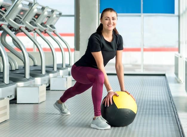 Vrouw in gymnastiek het ontspannen met geneeskundebal Premium Foto