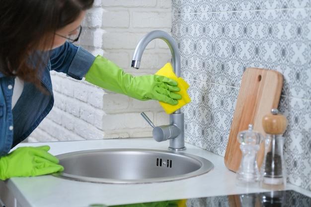 Vrouw in handschoenen met vod die huis in keuken schoonmaken. Premium Foto
